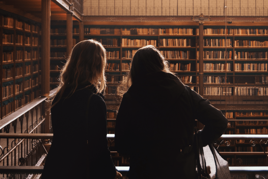 Photo of two women leaning over a balcony in a library