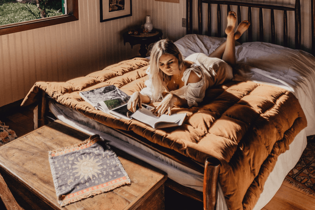 Person reading a book on a bed