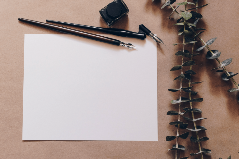 Photo of a blank page with calligraphy pins and eucalyptus