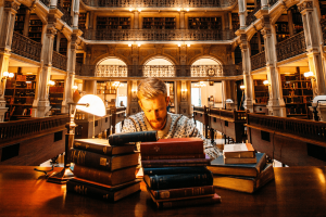 Photo of a man working at a desk in a library