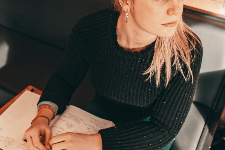 Photo of person looking worried and writing in a notebook