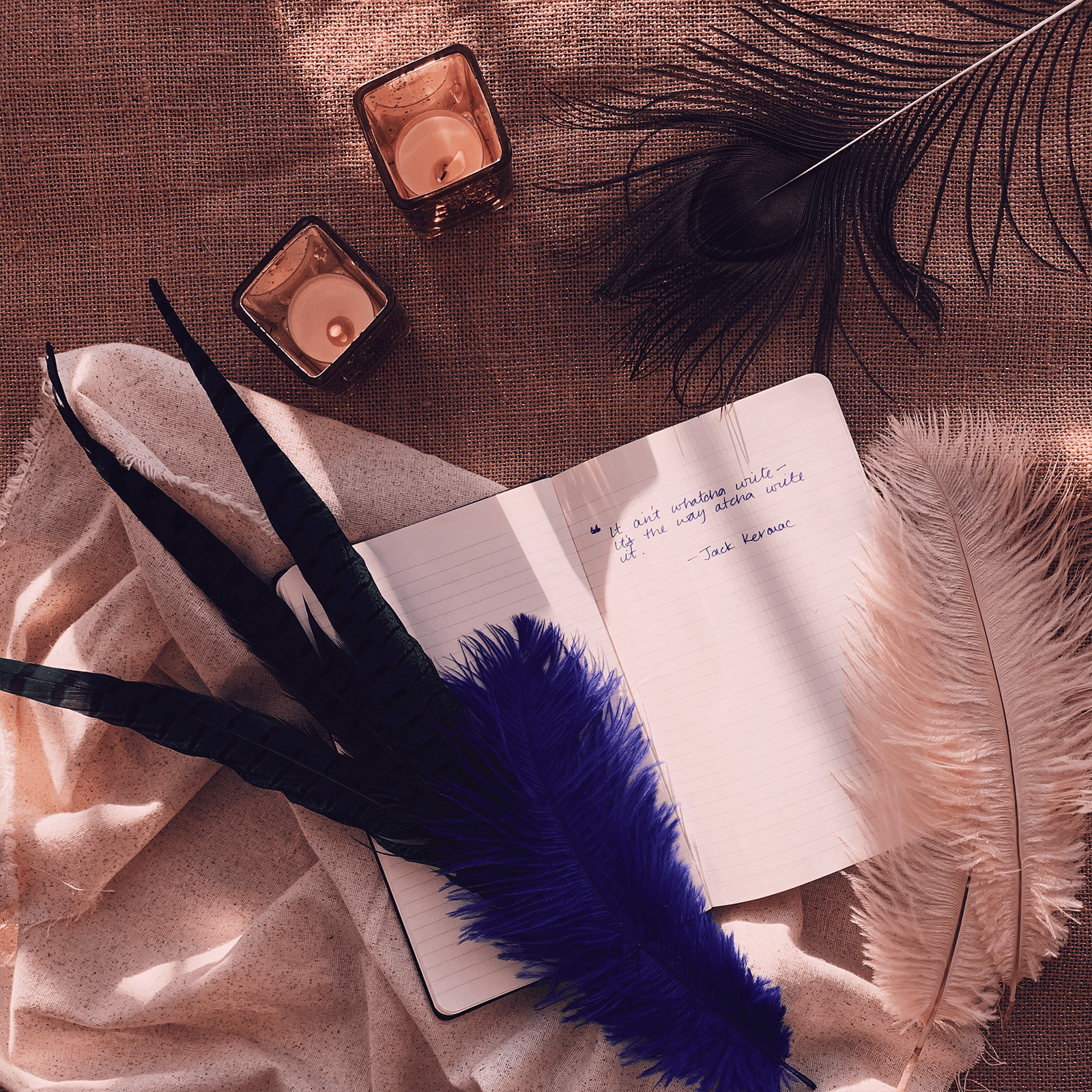 Flatlay photo of notebook, candles, and feather