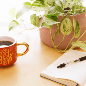Photo of a desk with a coffee cup and potted plant.